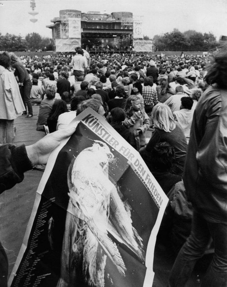 """Hamburg, St. Pauli Stadion, 2. September 1983 Publikum im Stadion mit dem Plakat """"Künstler für den Frieden"""" 1983 von Holger Matthies"""